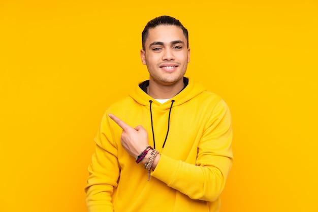 Knappe die mens bij het gele muur groeten met hand met gelukkige uitdrukking wordt geïsoleerd Premium Foto