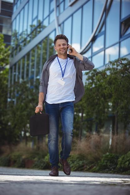 Knappe directeur die op mobiele telefoon spreekt Premium Foto