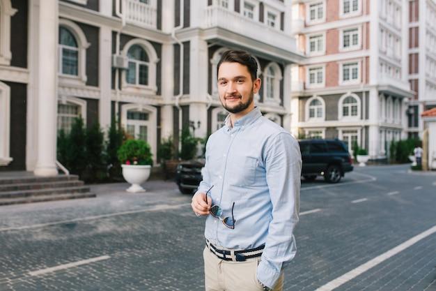 Knappe donkerharige man in blauw shirt loopt rond in britse wijk. hij heeft een zonnebril Gratis Foto