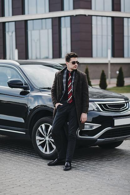 Knappe elegante man in zakelijke slijtage staande in de buurt van zijn moderne auto Premium Foto