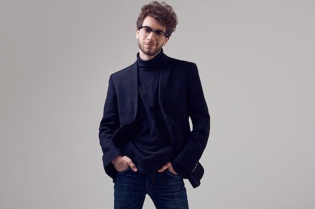 Knappe elegante man met krullend haar dragen pak en bril Premium Foto