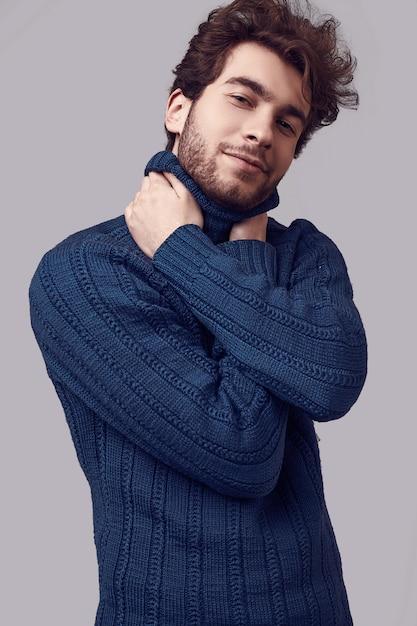 Knappe elegante man met krullend haar in blauwe trui Premium Foto