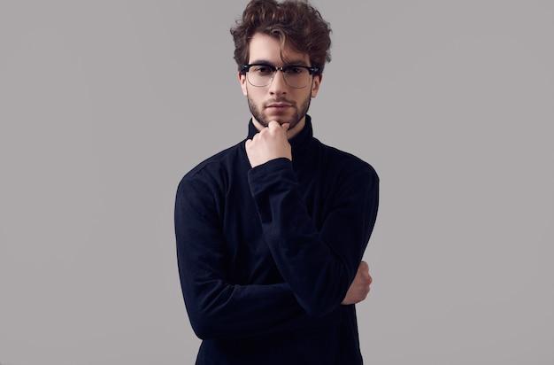Knappe elegante man met krullend haar zwarte coltrui en glazen dragen Premium Foto