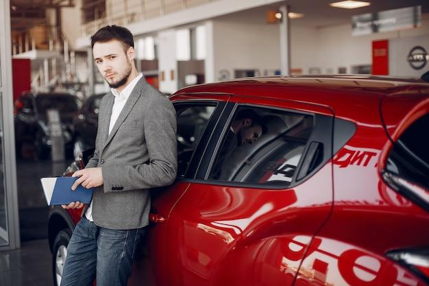 Knappe en elegante man in een autosalon Gratis Foto