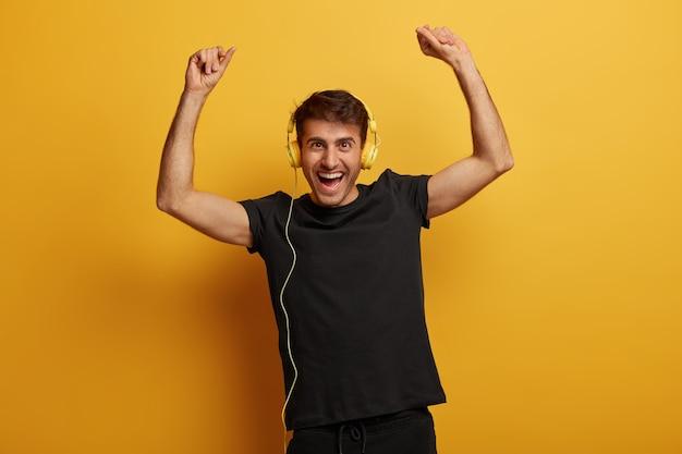 Knappe energieke man heft de armen op van geluk, draagt een headset, zingt samen met favoriete liedje, gekleed in een zwart t-shirt, heeft dolgelukkig uitdrukking, geïsoleerd op gele achtergrond Gratis Foto