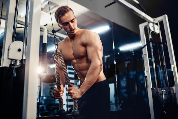 Knappe gespierde fitness bodybuilder die zware oefening voor triceps doet Premium Foto