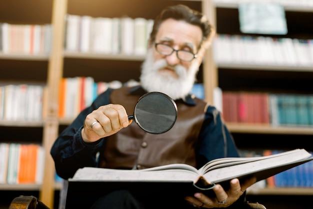 Knappe glimlachende bebaarde man, bibliothecaris of professor, in de bibliotheek, zittend op de achtergrond van boekenkasten, met vergrootglas en leesboek. focus op het glas en boek Premium Foto