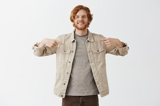 Knappe glimlachende bebaarde roodharige man poseren tegen de witte muur Gratis Foto