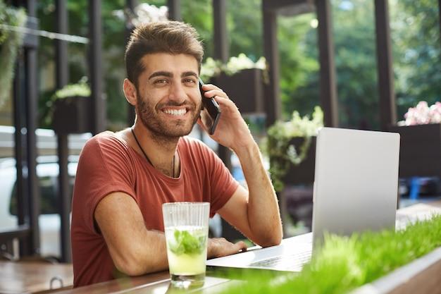 Knappe glimlachende man praten op de mobiele telefoon, de verkoper bellen die hij online vond tijdens het gebruik van laptop, winkelen, appartement op internet zoeken Gratis Foto