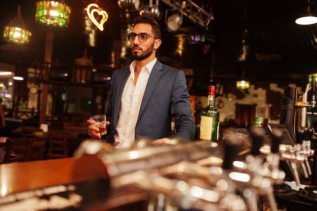 Knappe goed geklede arabische man met glas whisky en sigaar gesteld in pub. Premium Foto