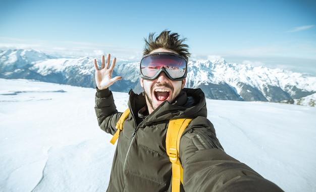 Knappe grappige skiër neemt een selfie in de winter in de sneeuw op een berg Premium Foto