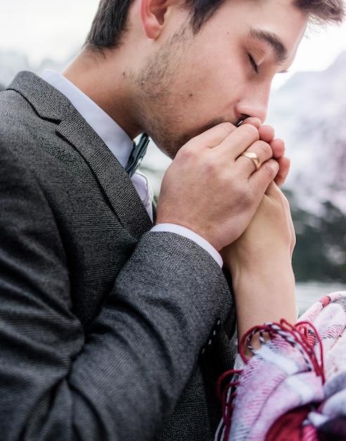 Knappe husbant kust teder de handen van de vrouw met gesloten ogen, gelukkig huwelijk Gratis Foto