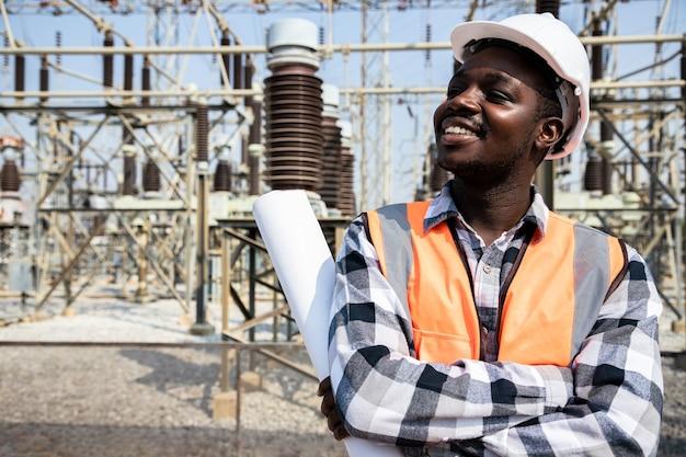Knappe ingenieur man met papieren projecten plannen en veiligheidshelm dragen voor high power plant. achteraanzicht van aannemer op achtergrond van elektriciteitscentralegebouwen. Premium Foto