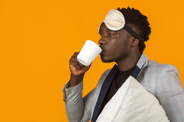 Knappe jonge afrikaanse man in blazer met kussen en mok Premium Foto