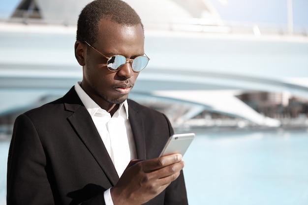 Knappe jonge afro-amerikaanse kantoormedewerker in elegant zwart pak en brillen staande in stedelijke omgeving, op zoek geconcentreerd terwijl proberen taxi te bellen met behulp van online app op zijn mobiele telefoon Gratis Foto