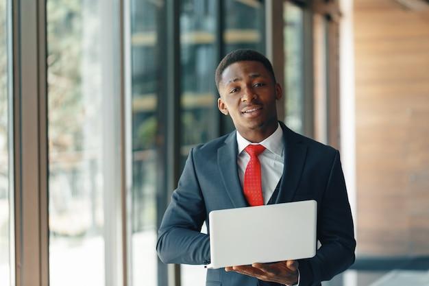 Knappe jonge afro-amerikaanse zakenman in klassieke pak met een laptop en glimlachen Premium Foto