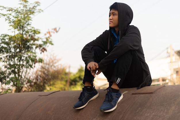 Knappe jonge aziatische man met capuchon zittend op een betonnen pijp en dromerig wegkijken Gratis Foto