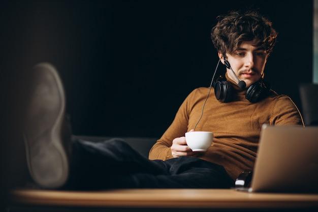 Knappe jonge bedrijfsmens die aan computer werkt en koffie drinkt Gratis Foto