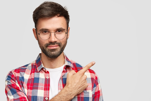 Knappe jonge europese man met haren, wijst naar de rechterbovenhoek met wijsvinger Gratis Foto