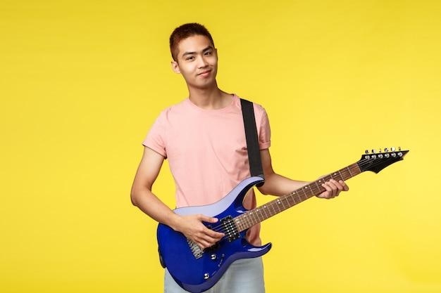 Knappe jonge geïsoleerde gitaar spelen en musicus, zingen Premium Foto