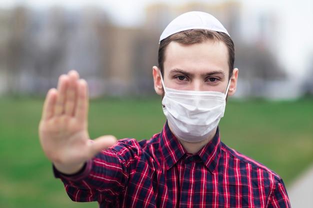Knappe jonge joodse man in traditionele joodse mannelijke hoofdtooi, hoed, boem of jiddisch op hoofd. man in medische masker op zijn gezicht met palm, stopbord tegen coronavirus, virus pandemie. covid-19 Premium Foto