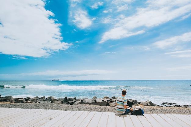 Knappe jonge kerel de fotograaf die met laptop op het strand werkt Premium Foto
