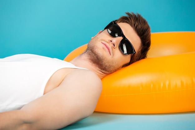 Knappe jonge kerel in zonnebril ontspannen op opblaasbare ring Gratis Foto