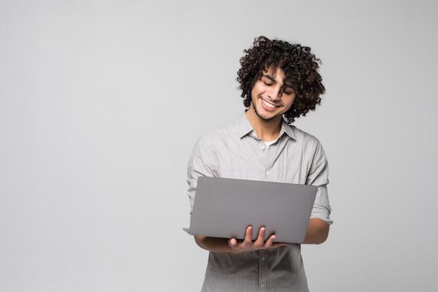 Knappe jonge krullende mens die zich met laptop computer bevindt die op een witte muur wordt geïsoleerd Gratis Foto