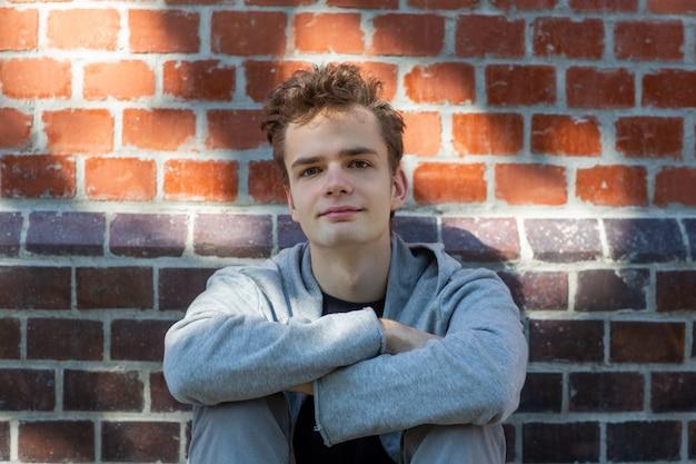 Knappe jonge lachende jongeman, tiener in een hoodie zit in de buurt van een bakstenen muur in de straat Premium Foto