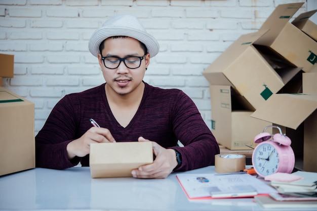 Knappe jonge man aan het werk met papieren Gratis Foto