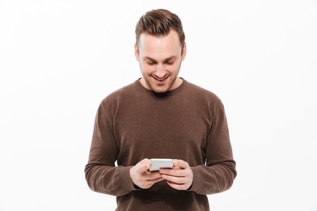 Knappe jonge man chatten via de mobiele telefoon Gratis Foto