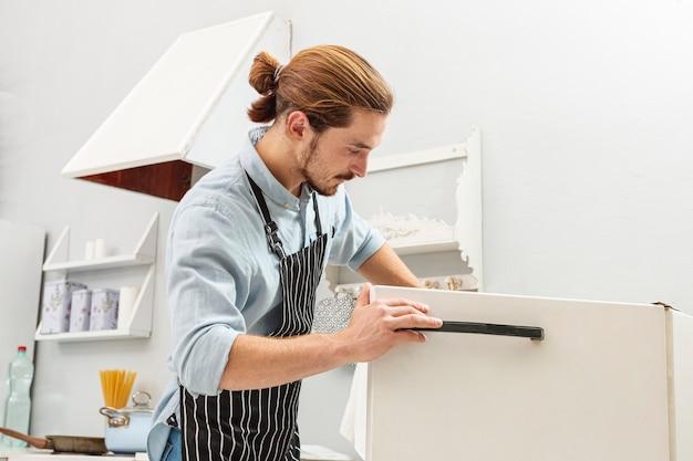 Knappe jonge man die een koelkast opent Gratis Foto