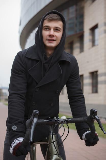 Knappe jonge man fietsten in de stad Premium Foto