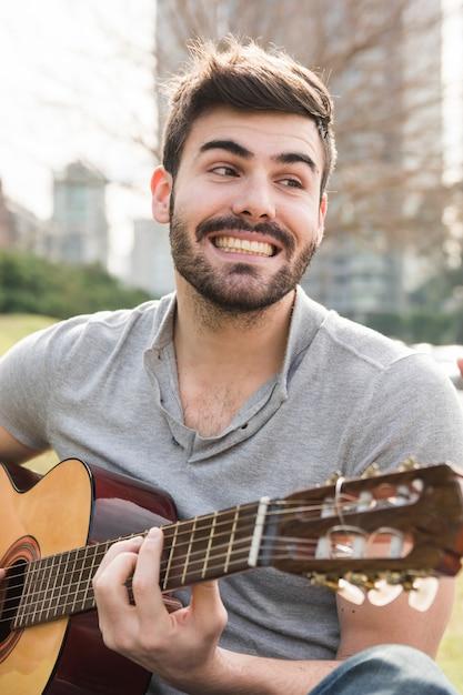 Knappe jonge man gitaarspelen glimlachend buitenshuis Gratis Foto