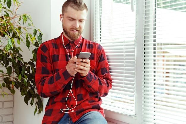 Knappe jonge man in koptelefoon met mobiele telefoon Premium Foto