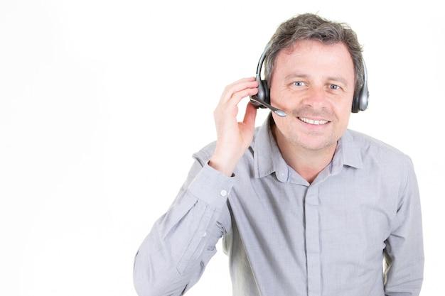 Knappe jonge man in werk in callcenter met koptelefoon op wit met kopie ruimte Premium Foto