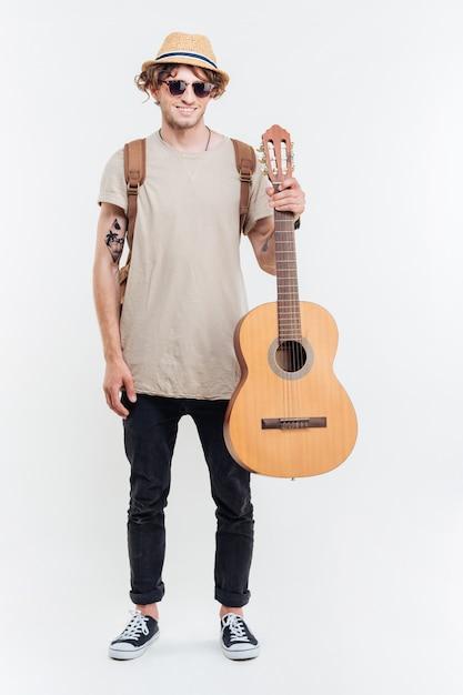 Knappe jonge man in zonnebril houden op de gitaar geïsoleerd op een witte achtergrond Premium Foto