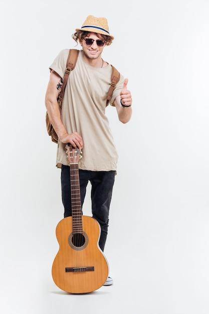 Knappe jonge man in zonnebril houden van de gitaar en duimen opdagen geïsoleerd op een witte achtergrond Premium Foto