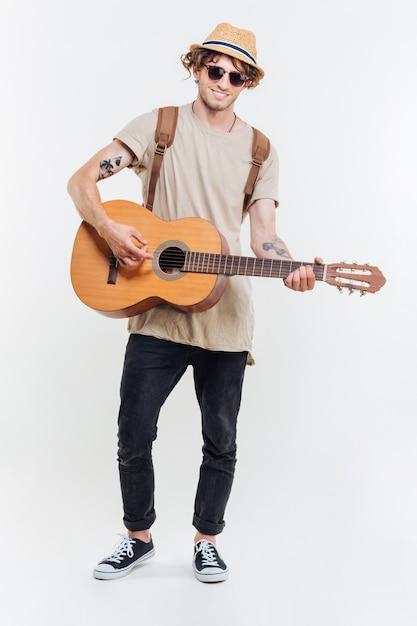 Knappe jonge man in zonnebril spelen op de gitaar geïsoleerd op een witte achtergrond Premium Foto