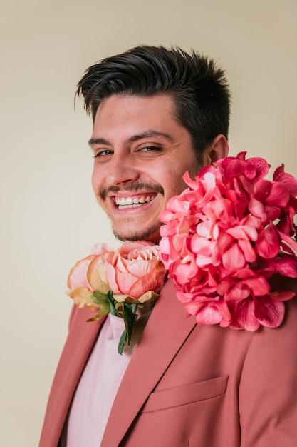 Knappe jonge man kijkt en glimlacht met bloemen om zijn nek, gekleed in een roze pak Premium Foto