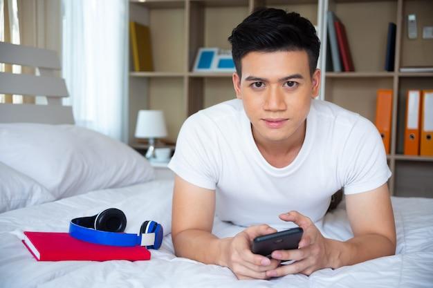 Knappe jonge man liggend op bed en gebruik smartphone Gratis Foto