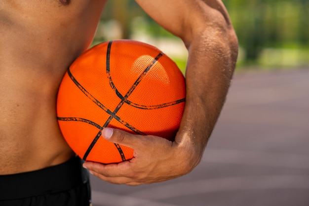 Knappe jonge man met een basketbal Gratis Foto