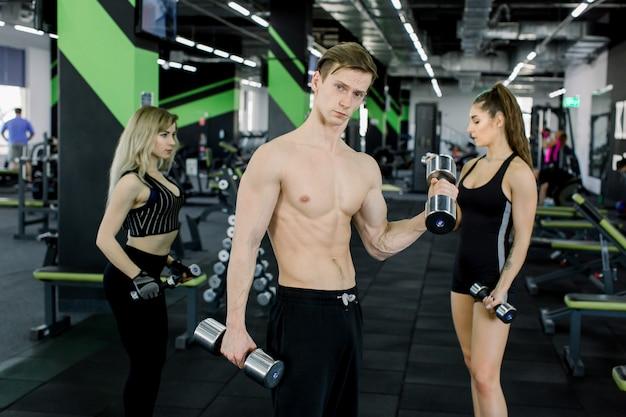 Knappe jonge man met gespierde naakte torso staande in de sportschool en traint biceps met halters samen met twee mooie jonge vrouwen op de achtergrond Premium Foto