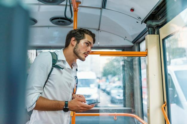 Knappe jonge man met smartphone in de bus Premium Foto
