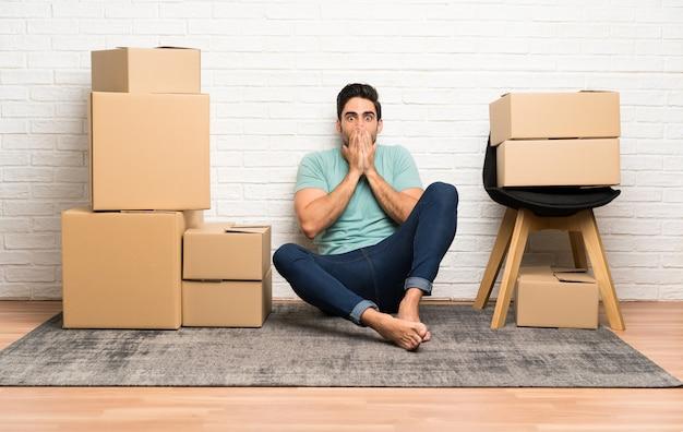 Knappe jonge man verplaatsen in nieuwe huis onder dozen met verrassing gelaatsuitdrukking Premium Foto