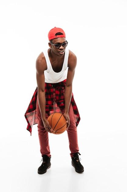 Knappe jonge mens die en zich met basketbalbal bevindt speelt Gratis Foto