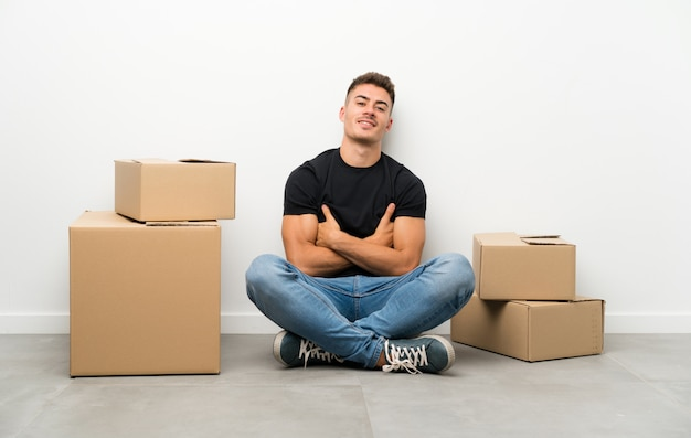 Knappe jonge mens die zich in nieuw huis onder dozen het lachen beweegt Premium Foto