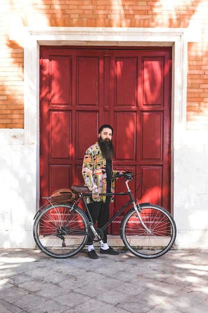 Knappe jonge mens met fiets die zich voor houten rode deurmuur bevindt Gratis Foto
