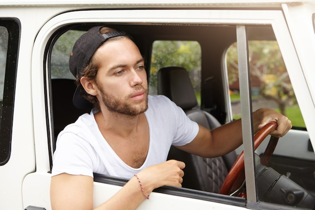 Knappe jonge ongeschoren man met casual t-shirt en baseballpet achteruit kijkend uit het open raam van zijn voertuig met vierwielaandrijving, op safari Gratis Foto