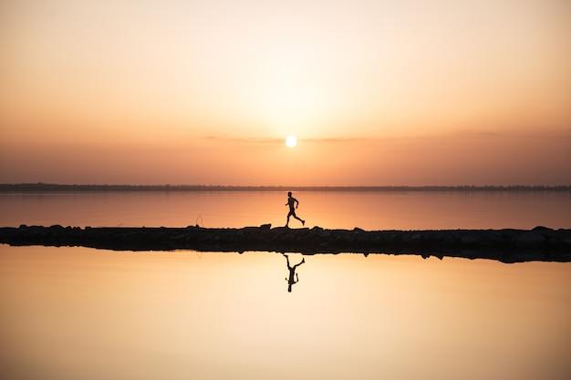 Knappe jonge sportman die bij het strand loopt Gratis Foto